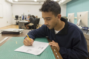 Male student drawing in class