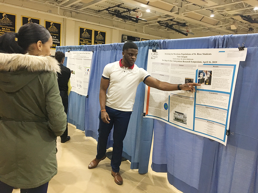 Biology student Victor Aisogun presenting his study in the gymnasium