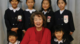 Toshiko Tanaka, Saint Rose Class of 1963, posing with children at her school in Japan, where she is vice principal