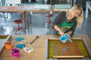 Printmaking student pouring paint in the studio