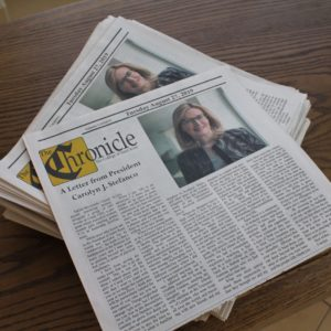 Copies of the Saint Rose Chronicle student newspaper with an article written by President Carolyn J. Stefanco at the top of the paper.