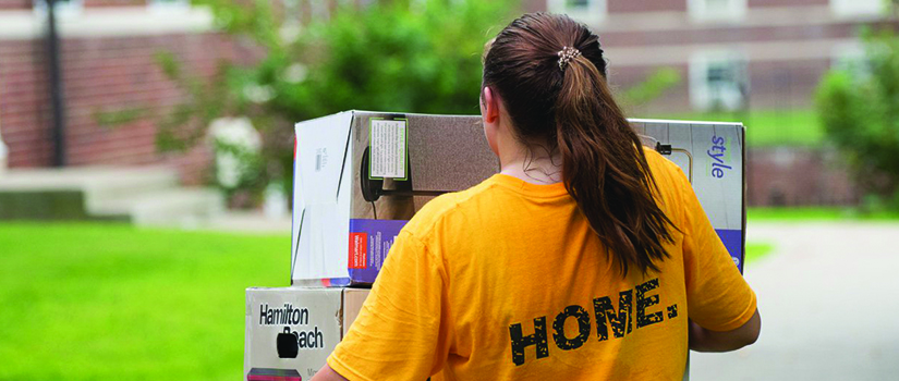 Saint Rose student wearing HOME shirt and carrying large boxes on move-in day