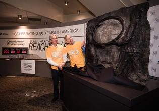 Tomomi Nakamura, Chairman and CEO, and Thomas J. Doll, President and Chief Operating Officer, take a closer look at the 3-by-4-foot, 300-pound bronze plaque, produced by local artist Chad Fisher, commemorating Subaru of America's 50th Anniversary.