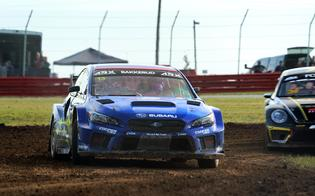 Andreas Bakkerud negotiates a narrow dirt section of the Mid-Ohio rallycross circuit ahead of rival Tanner Foust.