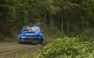 Gravel erupts out from the wheels of the #199 WRX STI as it slides sideways through the forest during testing.