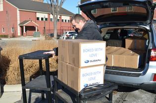 Subaru staff unpack boxes of school supplies for Cream teachers
