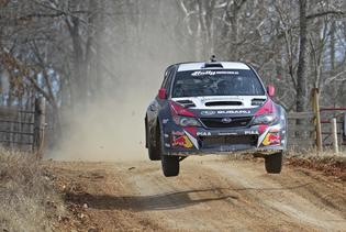 Travis Pastrana and codriver Chrissie Beavis jump at 100 acre Wood Rally 2014