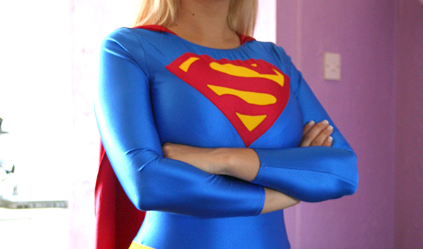 Supergirl with her arms folded across her breasts