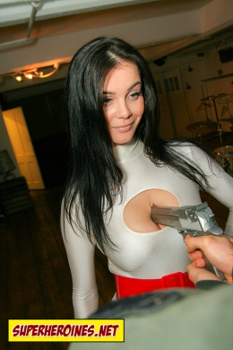 Man pressing a gun into Power Girls breasts