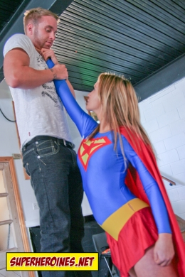 Supergirl lifting up a madman by his throat