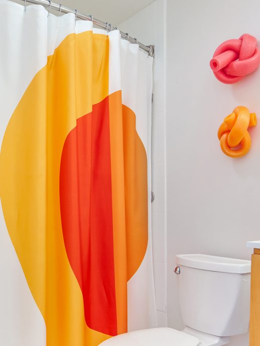 Bathroom with shower, and pool noodles tied in knots hanging on the wall