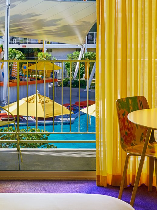 View of balcony with and pool area from hotel room with chair