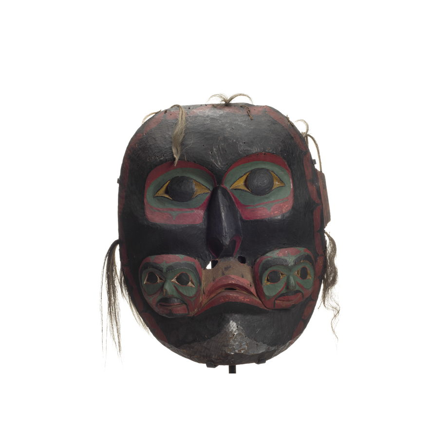 Imas - Three-Faced Mask, large dark ancestral spirit mask two small faces carved at either side of mouth, black with green red and white details, some hair fragments