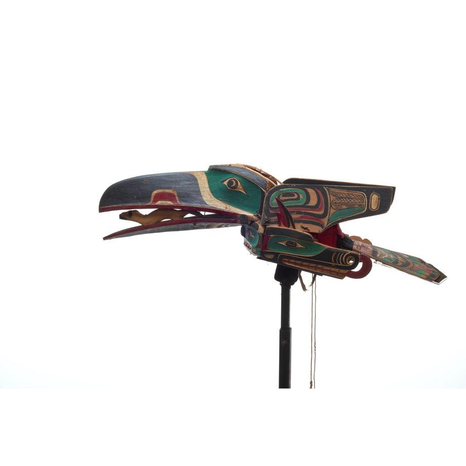 D'une coiffe de corbeau peinte et sculptée aux ailes articulées, une hermine sculptée dans le bec, sur une armature sculptée de serpent Sisiyutł.