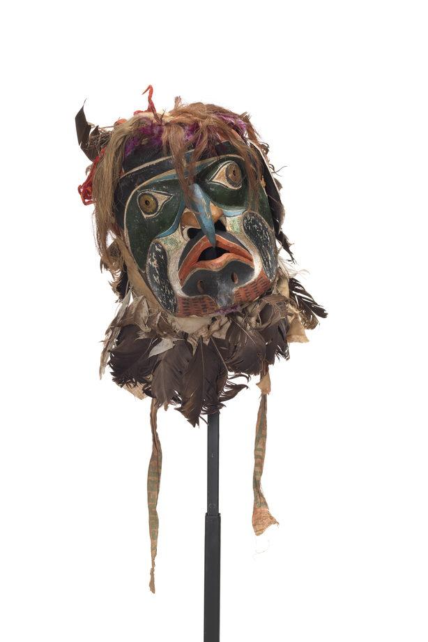 D'un masque de Bakwas au nez bleu en bec crochu, des disques de laiton perforés sur les yeux ceints d'une orbite vert foncé, des marques faciales rouges, blanches et noires, un voile couvert de plumes et de poil, des rubans de couleur vive, des oreilles pointues.