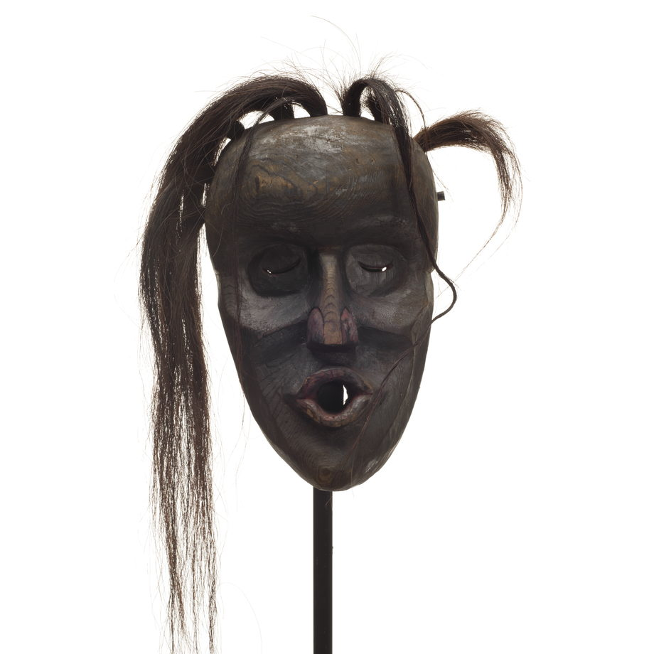 Dzunukwa or wild woman of the woods mask, deep carved, dark smoky paint with dark red on nose and pursed lips, tufts of hair falling to one side