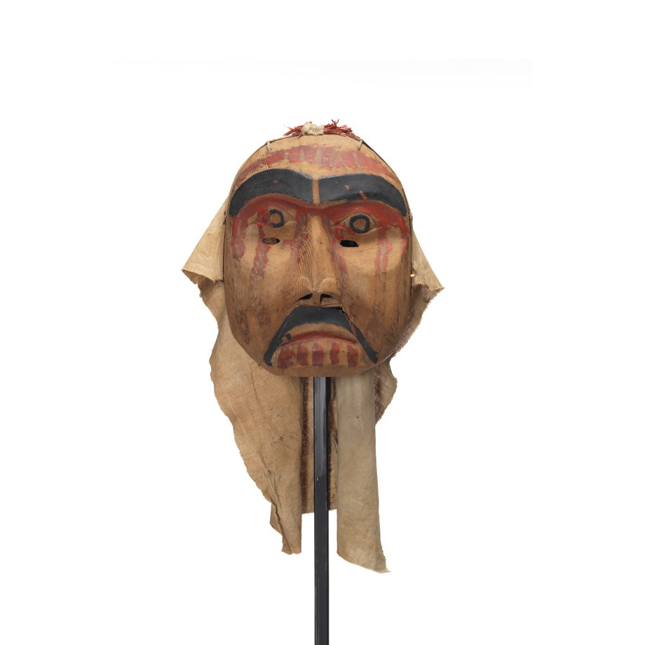Mourning mask red paint drips on forehead, cheeks and chin. Black moustache and eyebrows. Eye holes on upper cheek.