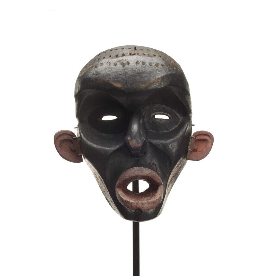 Un masque d'Ogresse Dzunukwa, sculpture profonde, peint en noir, lèvres, joues et oreilles rouges, le crâne percé de trous pour des touffes de cheveux.