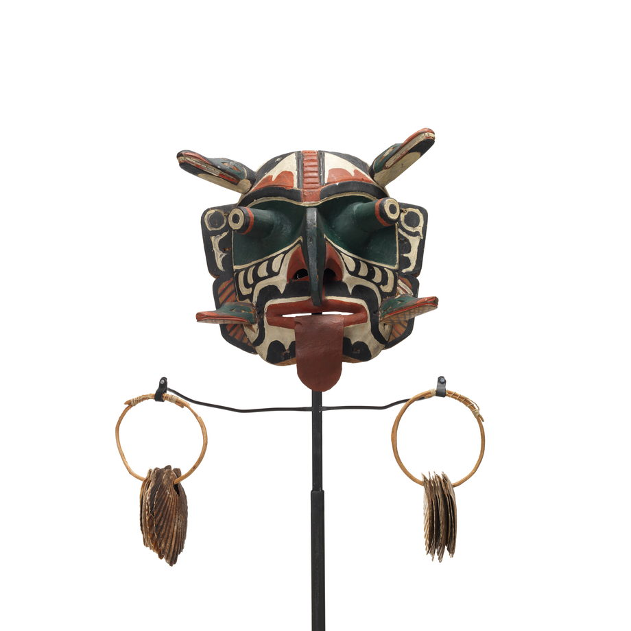 Xwixwi mask representing red snapper or cod, shown with sea shell rattles. Large protruding eyes, drooping tongue, 4 animal figures project from temples and cheeks