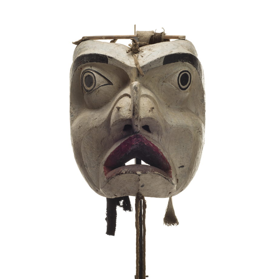 Forest spirit mask, mostly white face, deeply carved features, black paint eyebrows and around eyes, cloth and leather strips attached to back
