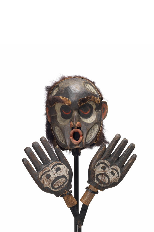 A Dzunukwa or wild woman of the woods mask with hands attached to mount, pursed lips painted red, mostly black with white paint details on face and hands