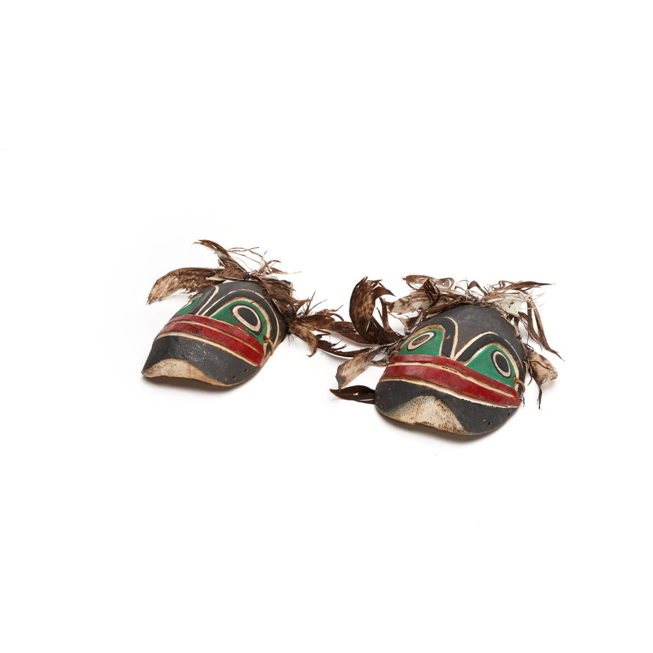 Kneecaps with frog faces, feathers attached, part of Bak´was costume, black and green with red mouth