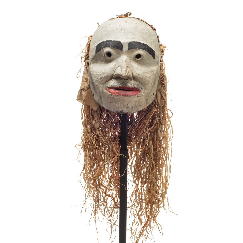 Forest spirit mask, humanoid features, mostly white face with red lips and prominent black eyebrows, cloth and cedar drape on back