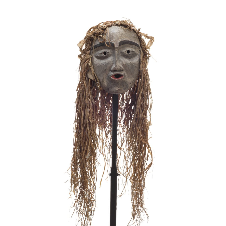 A small forest spirit mask, mostly white face, pursed red lips, prominent black eyebrows, long cedar trim draping from top and back