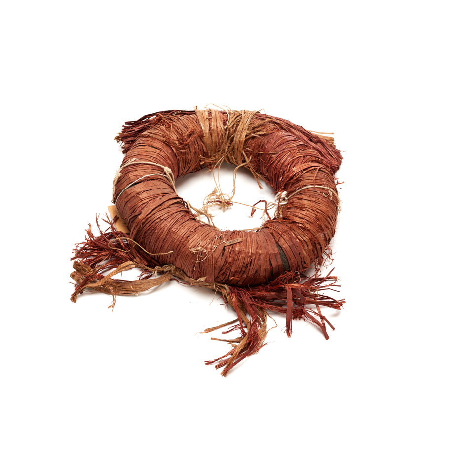 A torus shaped headdress of red cedar bark, formed by wrapping bark around wool loop, bundle of cedar front and two cedar tassels on back side