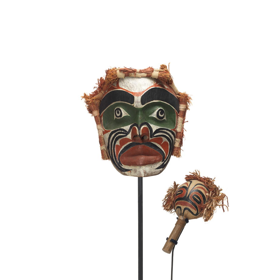 A Yadan or large rattle and Imas or Ancestor Mask painted in black, green, red and white with cedar bundles on top and sides