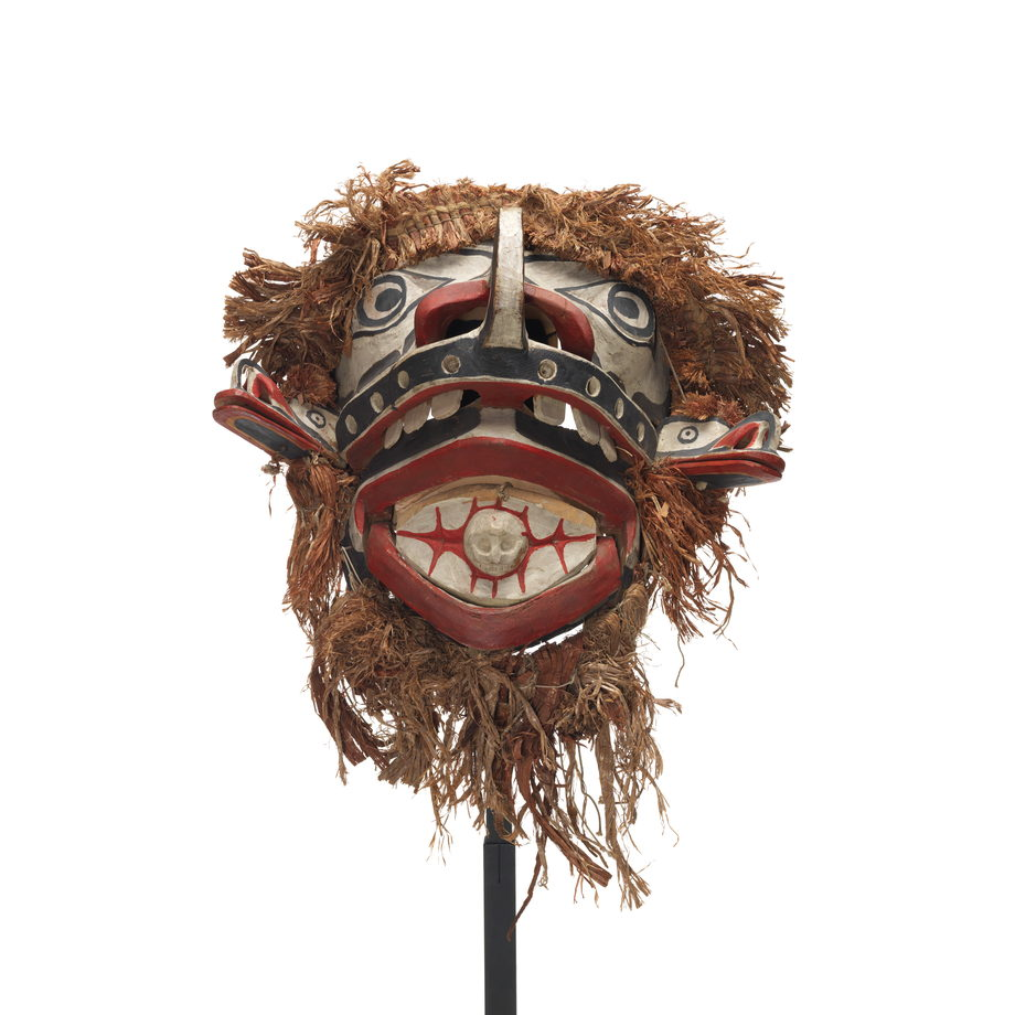 Baxwbakwalanuksiwe' mask, surrounded by cedar trim with two mouths, two protruding beak figures and skull figure in mouth.