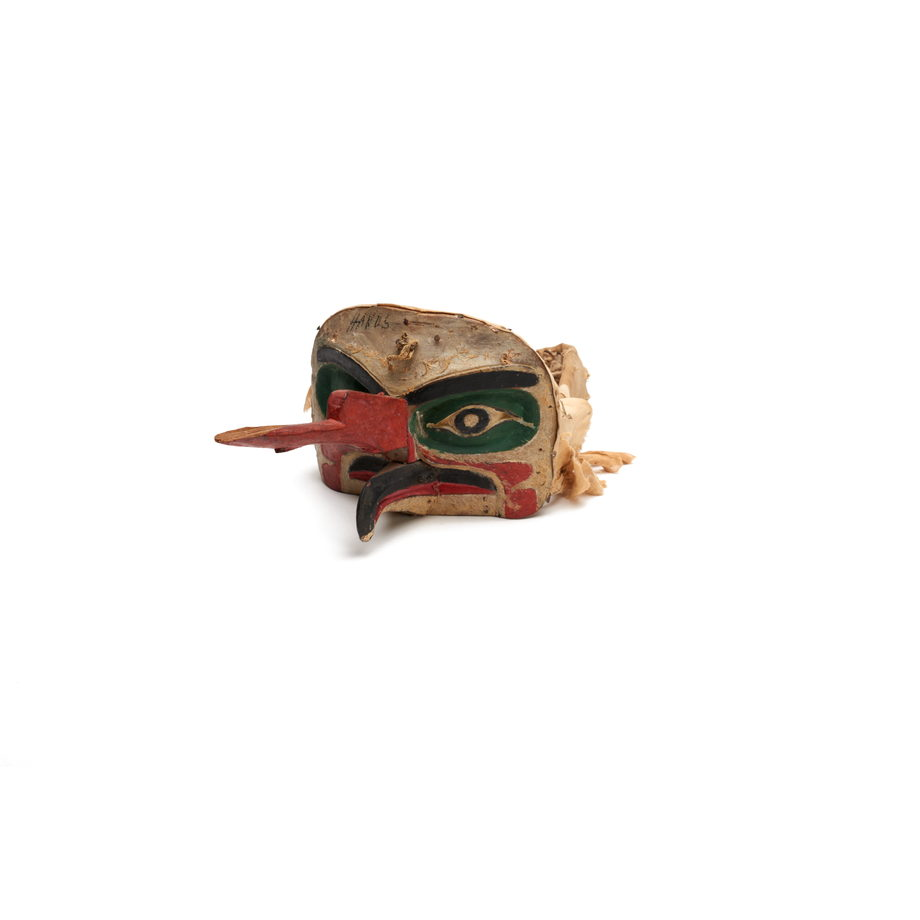 A 'Na'nalalał or weather mask, long red proboscis over a curved beak painted black with red edges, green patches around eyes, cloth head band