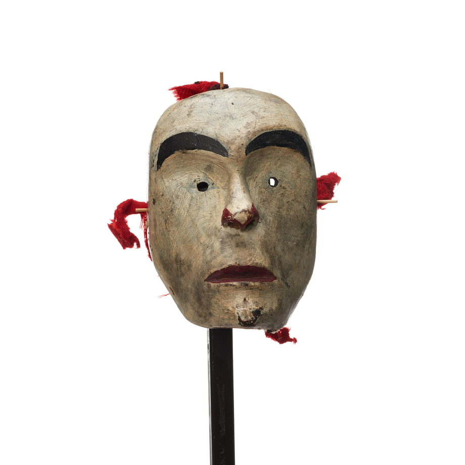 A white-faced mask, small circular eyeholes, red paint on lips and surrounding nostrils, bright red fabric rigging