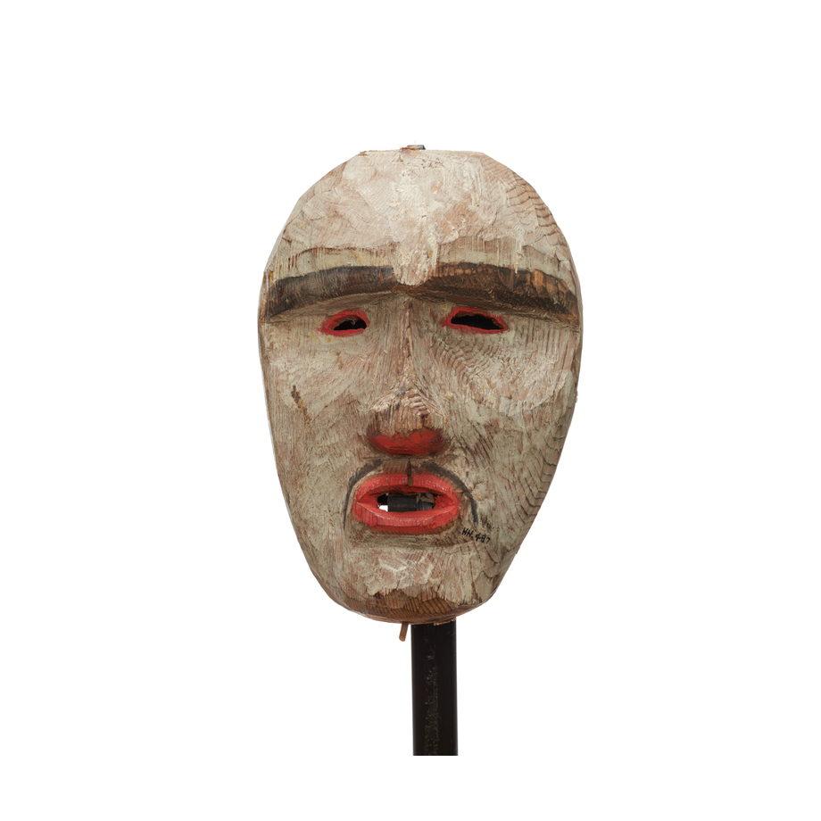 Un masque blanc, du rouge autour des yeux plissés percés, des narines et des lèvres, fine moustache et sourcils épais.
