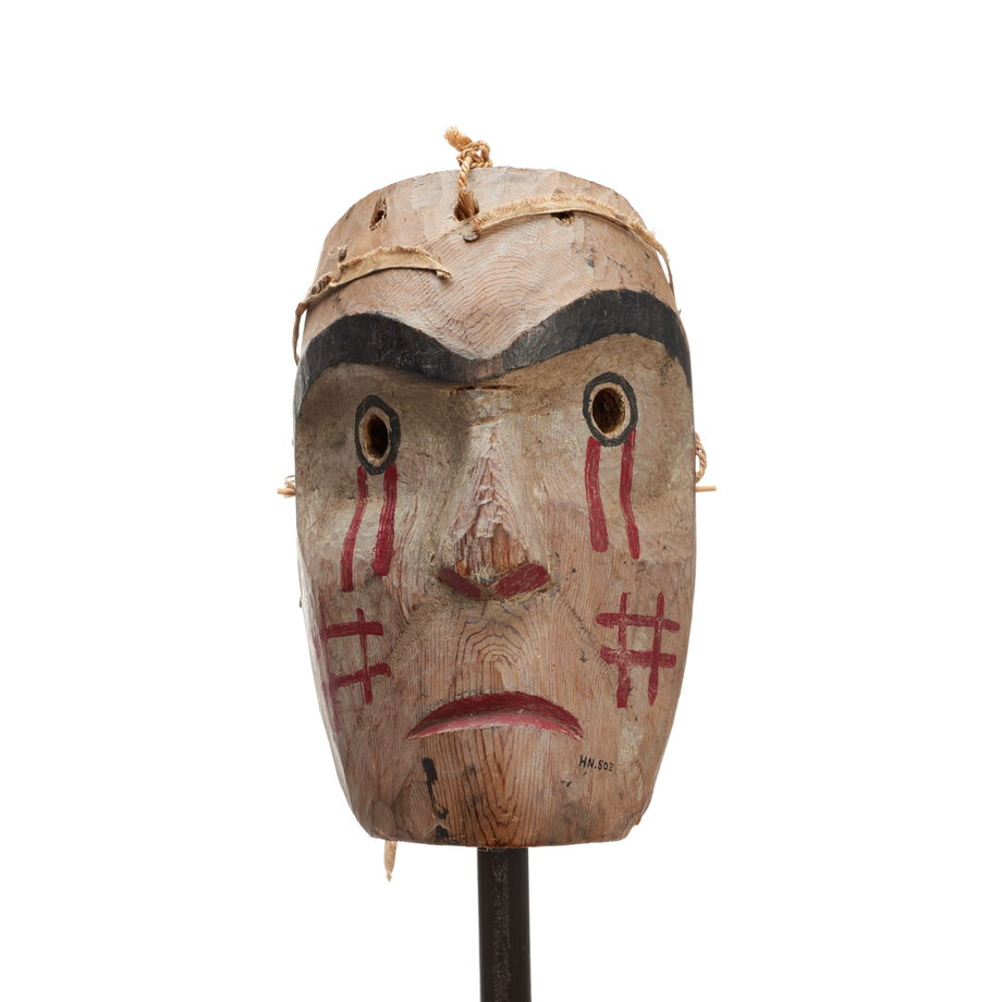 Kwasanuma or mourning mask, cedar with red drips of paint below eyes, cross-hatch pattern in red on cheeks, mournful expression