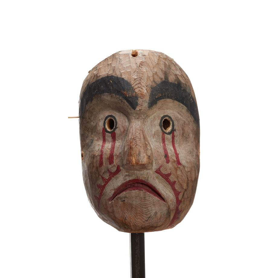 Kwasanuma mourning mask, carved of cedar with black eyebrows, round eyeholes, paint dripping from eyes and cheeks, mournful expression