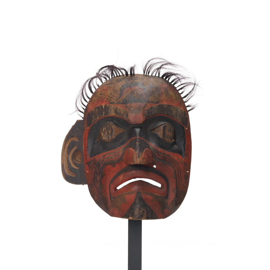Large deaf man mask, lacks eyeholes, tufts of horsehair above, black bands of paint around eyes, mostly red and black markings on face, sad expression