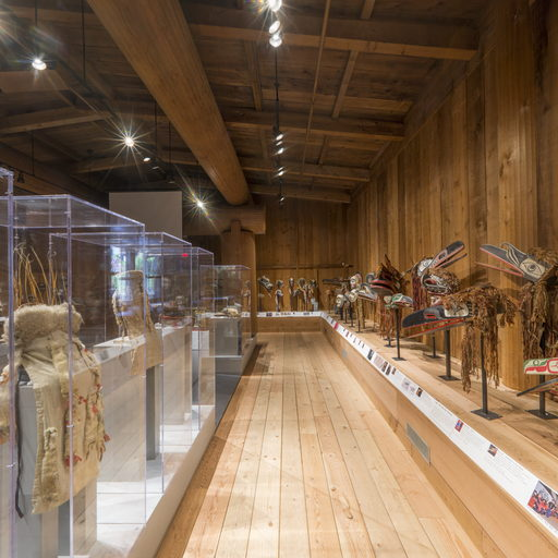 View of north side of the Potlatch Gallery, ceremonial regalia mounted along the wall to the right of the viewer.