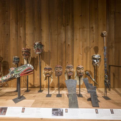 Image shows a section of the north side of the Potlatch Gallery in which a speaker's staff, a dzunakwa mask, four mourning masks and two copper shields are displayed.