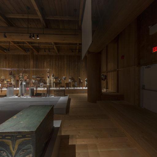 Vue d'un coin sombre de la galerie du potlatch, avec un coffre en cèdre au premier plan.