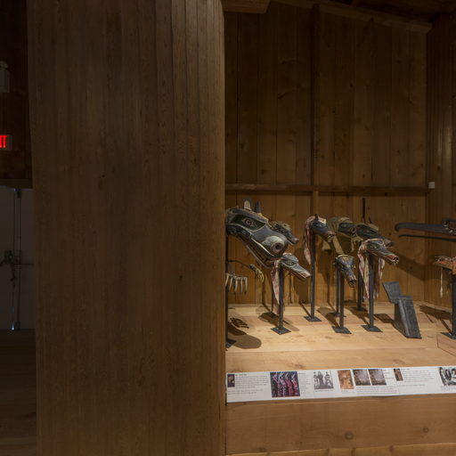 Corner of the Potlatch Gallery showing a large cedar post and a group of wolf masks.