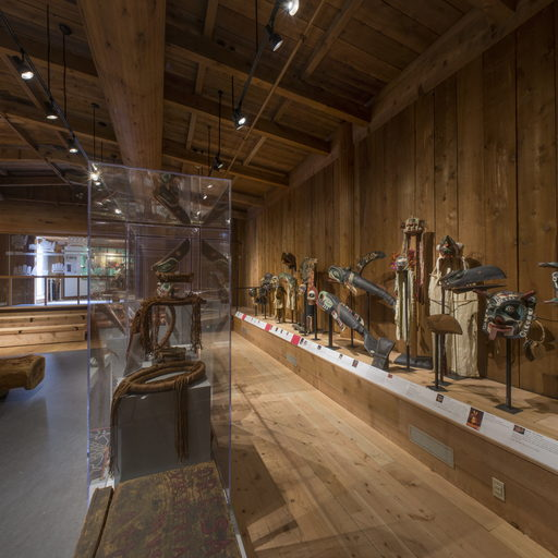 Image of the south side of the Potlatch Gallery showing a collection of potlatch regalia mounted against the wall.