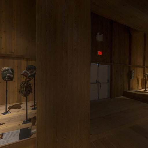 Image shows a darkened corner of the Potlatch Gallery with a group of Numaml masks on the left.