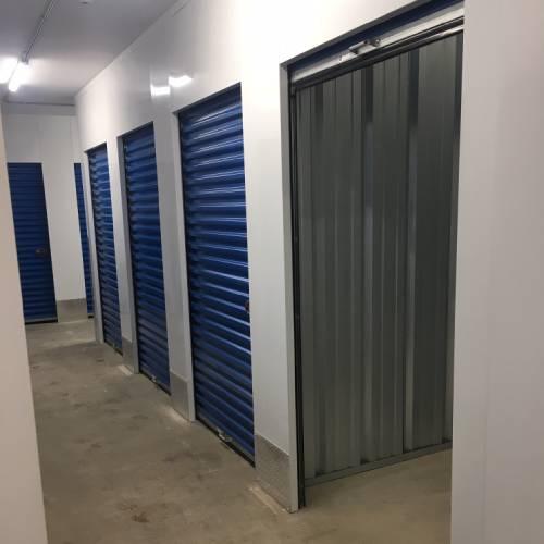Photograph of indoor self storage units with one door open