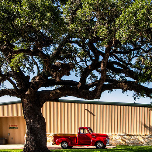 Front of Security Storage main building with a tree and red truck.