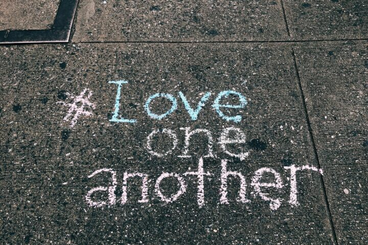love one another chalk written on concrete floor