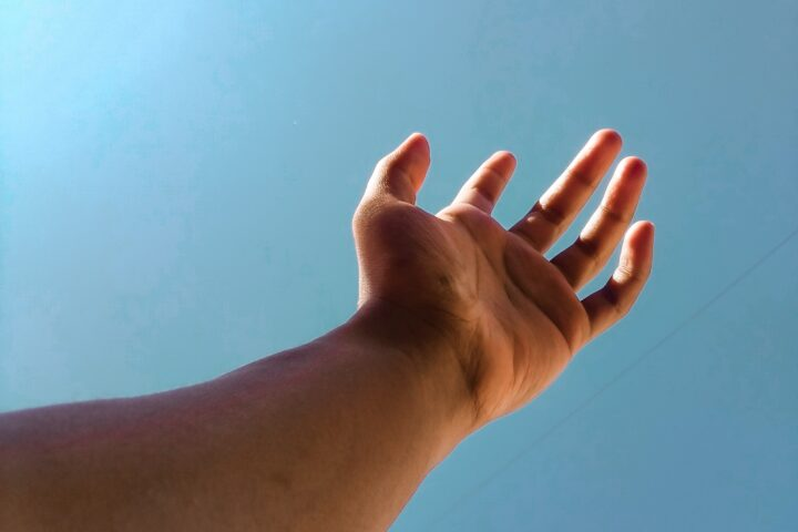 person raising right hand under blue sky during daytime