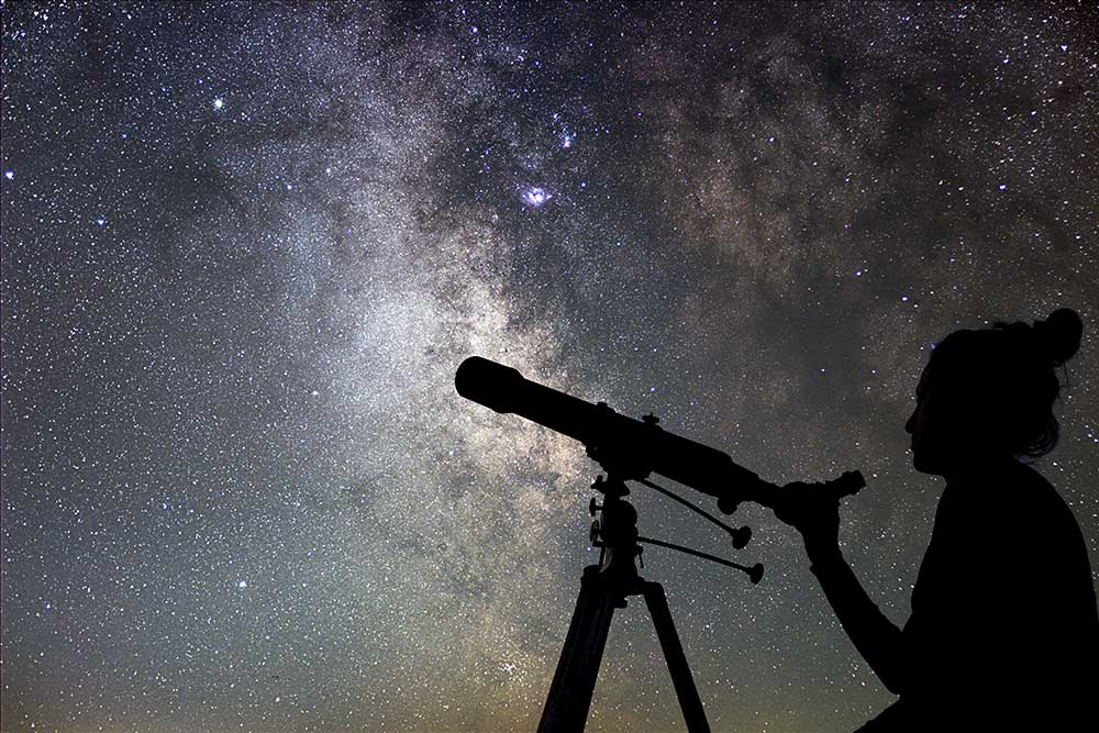 woman looking at the stars through telescope