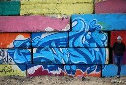 فنان يزين غزة برسوم الخط العربي