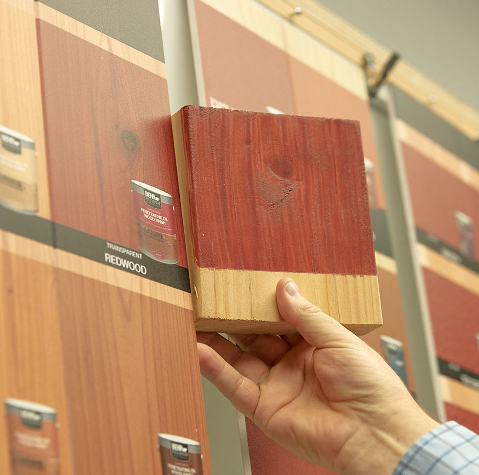 A Bernard Group employee color matches wood stain to print.